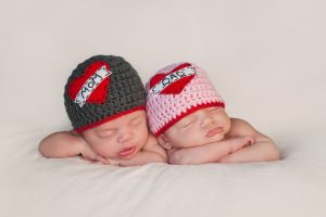 "Five week old sleeping boy and girl fraternal twin newborn babies. They are wearing crocheted ""Love Mom"" and ""Love Dad"" beanies."